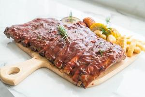 Grilled BBQ ribs with vegetables and french fries on wooden cutting board