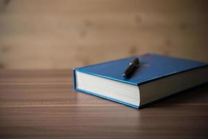 Book with a pen on wooden table photo