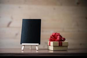 Pizarra en blanco, caja de regalo sobre fondo de madera con espacio de copia foto