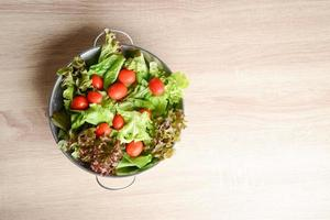 Fresh salad with vegetables and greens on wood table photo