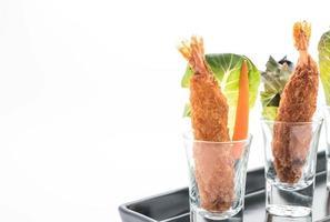 Langostinos rebozados fritos sobre fondo blanco. foto