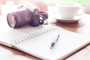 cuaderno con bolígrafo y cámara