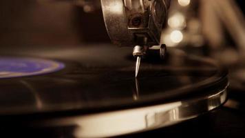 extreme Nahaufnahme der scharfen Nadel, die eine Vinylscheibe mit hellem wenig von der rechten Seite in 4k spielt