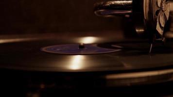 close-up extremo de agulha decorada tocando um disco de vinil em um toca-discos antigo com iluminação suave em 4k