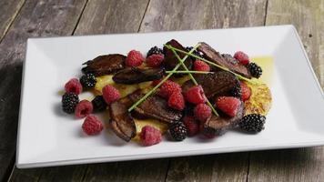colpo rotante di un delizioso piatto di pancetta affumicata d'anatra con ananas grigliato, lamponi, more e miele - cibo 094