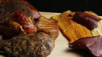 Rotating shot of a variety of delicious, premium smoked meats on a wooden cutting board - FOOD 054