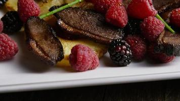 tomada rotativa de um delicioso prato de bacon de pato defumado com abacaxi grelhado, framboesas, amoras e mel video