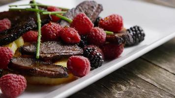 tomada rotativa de um delicioso prato de bacon de pato defumado com abacaxi grelhado, framboesas, amoras e mel - comida 101 video