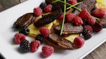 tomada rotativa de um delicioso prato de bacon de pato defumado com abacaxi grelhado, framboesas, amoras e mel - comida 116 video