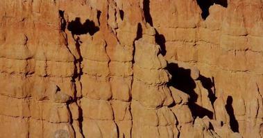 Toma panorámica lenta en la trayectoria diagonal de las paredes de roca natural en el paisaje de deser en 4k