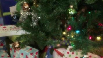 ein verpacktes Weihnachtsgeschenk, das unter einen geschmückten Weihnachtsbaum gelegt wird video
