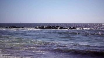 rochas na água atingidas por ondas 4k video