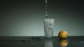 líquido transparente carbonatado que se vierte y salpica en cámara ultra lenta (1,500 fps) en un vaso lleno de hielo - líquido vertido 007