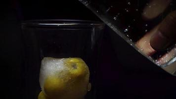 colocando un hielo con nance en agua mineral
