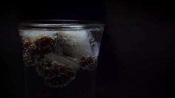 colocando un hielo con pasas en agua mineral