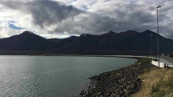 Carretera de montaña de Islandia cerca del lago con coches 4k