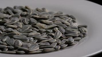 ripresa cinematografica e rotante di semi di girasole su una superficie bianca - semi di girasole 017 video