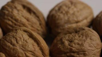 Cinematic, rotating shot of walnuts in their shells on a white surface - WALNUTS 022