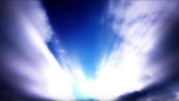 Sunbeams Stream Through Roiling Time Lapse Clouds in a Blue Sky