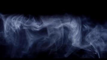 nuvens de fumaça movendo-se da esquerda para a direita expostas por um raio de luz na escuridão em 4k