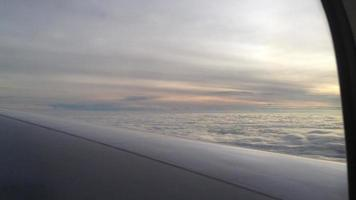 View of altostratus and stratocumulus clouds from the interior of a plane overlooking a wing at dusk