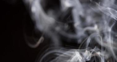 Detail mehrerer Fokalebenen aus weißem Rauch, die die Szene in 4k mit verschwommenen Spiralen im Vordergrund füllen video