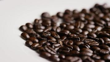 Foto giratoria de deliciosos granos de café tostados sobre una superficie blanca - granos de café 050