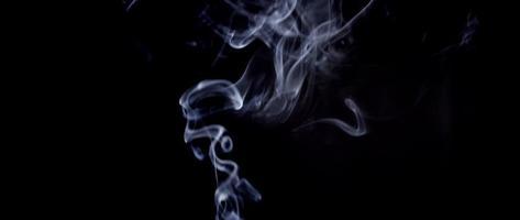 fumaça branca flutuando no centro e no lado esquerdo da cena na escuridão em 4k video