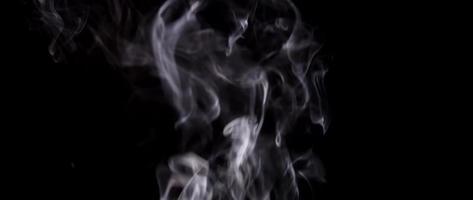 suaves nubes pequeñas de humo blanco subiendo y desapareciendo en la oscuridad en 4k