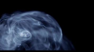 White smoke spinning and drawing mystical swirls on dak background in 4K