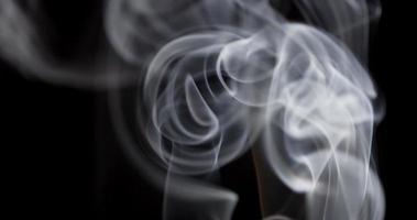 close-up extremo de linhas finas de fumaça branca desenhando espirais impressionantes em fundo escuro em 4k