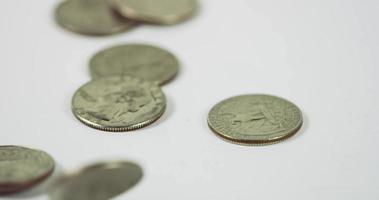 muitas moedas de um quarto de dólar caindo e girando sobre três moedas na mesa branca, seis moedas colocadas na cena em 4k