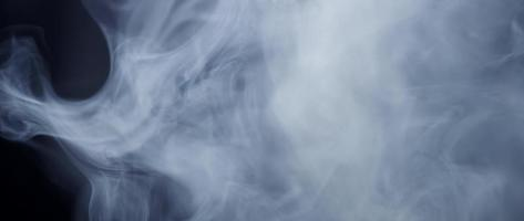 Focused foreground of smoke swirls dancing on defocused dark background in 4K