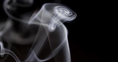 Cerca de finas líneas de humo bailando con movimientos hipnóticos sobre fondo oscuro en 4k