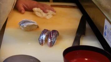 mano recogiendo sushi