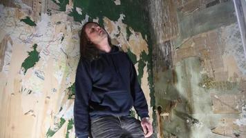 un hombre de mediana edad o un psicópata parado en la esquina de una vieja casa abandonada