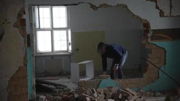Depressed and mad man throws stones in an old abandoned house