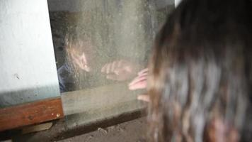 homem deprimido e zangado limpa a mão em um espelho sujo em uma velha casa abandonada video