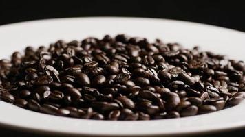 Foto giratoria de deliciosos granos de café tostados sobre una superficie blanca - granos de café 075