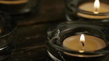 Velas de té con mechas en llamas sobre un fondo de madera - velas 009