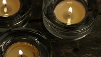 Velas de té con mechas en llamas sobre un fondo de madera - velas 024