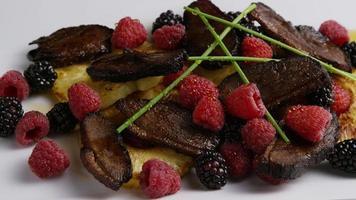 foto rotativa de um delicioso prato de bacon de pato defumado com abacaxi grelhado, framboesas, amoras e mel - comida 096 video