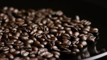 Foto giratoria de deliciosos granos de café tostados sobre una superficie blanca - granos de café 022