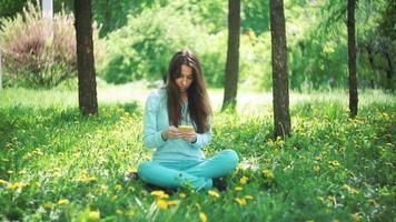 mujer con teléfono sentado en la hierba