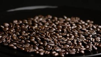 Foto giratoria de deliciosos granos de café tostados sobre una superficie blanca - granos de café 021