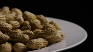 Cinematic, rotating shot of peanuts on a white surface - PEANUTS 027