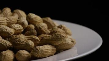 filme cinematográfico giratório de amendoim em uma superfície branca - amendoim 027
