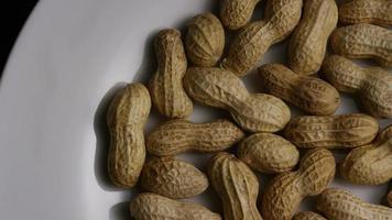 tiro cinematográfico giratório de amendoim em uma superfície branca - amendoim 003