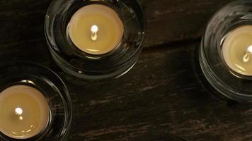 Velas de té con mechas en llamas sobre un fondo de madera - velas 013