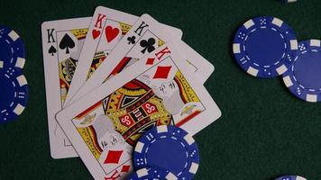 Foto giratoria de cartas de póquer y fichas de póquer sobre una superficie de fieltro verde - póquer 012